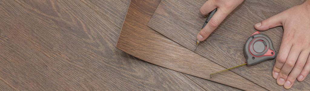 Vinyl flooring installation. Easy installation and cutting with a knife, Master cuts vinyl plank before installation, brown heated floor